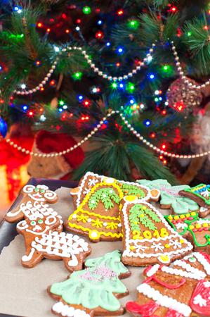 Domácí vánoční strom tvaru perník cookies na troubě mitten. Osvětlené slavnostní pozadí. Vícebarevný vertikální obraz v interiéru. Reklamní fotografie