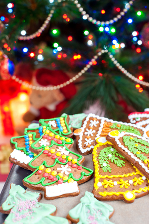 Homemade christmas tree shape gingerbread cookies on oven mitten. Illuminated festive background. Multicolored vertical indoors image. Stock Photo