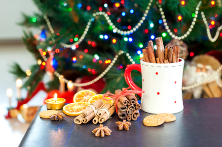 Cinnamon sticks, anise stars and gingerbread cookie on illuminated christmas tree background. Festive indoors still-life. Colored horizontal image. Stock Photo