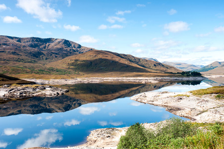 panoramas: Landscape with beautiful scottish wild mountains and lake with reflection. Panoramic view. Loch Cluanie fort William. Scotland. Uk. Vibrant colored summertime outdoors horizontal image with cloudy sky background.