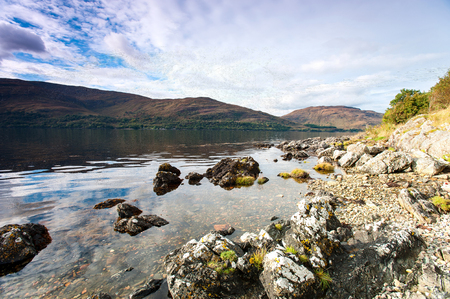 panoramas: Landscape with beautiful scottish wild mountains and lake with reflection. Panoramic view. Loch Cluanie fort William. Scotland. Uk. Low, wide angle view. Vibrant colored summertime outdoors horizontal image with cloudy sky background. Stock Photo