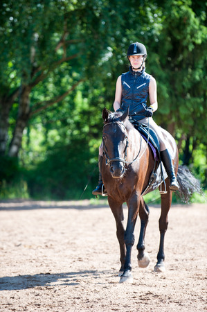Young teenage lady equestrian riding horseback at equestrian school. Multicolored vibrant outdoors vertical summertime image