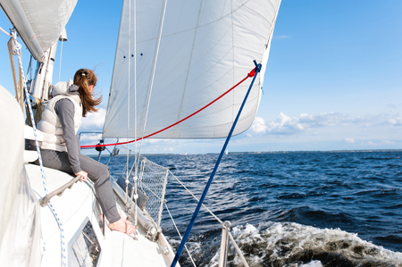Young girl having trip on sailing yacht at a speed swimming in wind through blue sea. Outdoors horizontal colored image. Vide angle view. Stock Photo