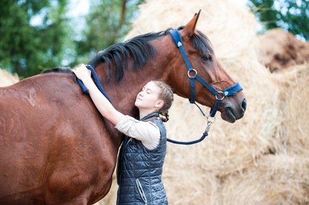 Young cheerful teenage lady equestrian hugging with love her favorite chestnut horse at ranch. Vibrant colored outdoors horizontal summertime image.