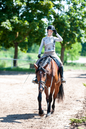 Training is finished. Young teenage girl riding a horse on arena at equestrian school. Colored outdoors vertical summertime image Stock Photo