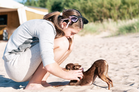 Young teenage girl scratching her lovely dog's back sitting at summer beach. Colored vibrant horizontal outdoors image.