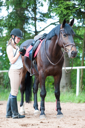 Young teenage girl owner with her chestnut stallion wairing for sport training. Colored vertical outdoors image.
