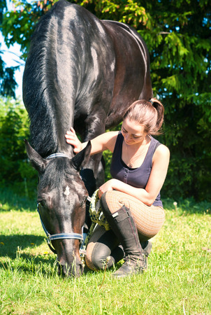 Young lady equestrian sitting and stoking her favorite black horse on green grass. Vibrant multicolored summertime outdoors vertical image.
