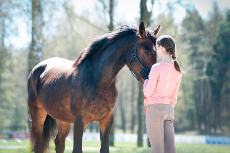 Young teenage girl standing with her favorite brown horse. Colored outdoors horizontal springtime image. Light vintage filter.