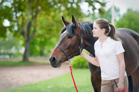 Best friends. Young teenage girl owner together with her favorite brown horse looking forward. Vibrant colored outdoors horizontal image. Slightly filtered. Stock Photo