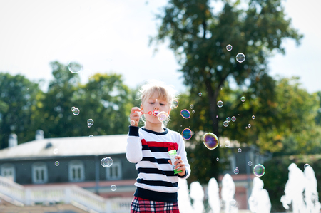 Little blondy girl playing with soap bubbles in the green summer park. Colored outdoors horizontal image. Stock Photo