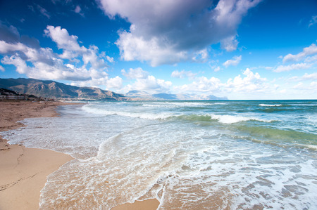 Alcamo marina, Sicily, Italy, Europe. Castellammare del golfo. Beautiful cloudy blue sky above mountains and curly waves of Tyrrhenian sea. Summertime outdoors horizontal colored image. Wide angle view.