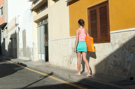 Young teenage girl walking with surfboard from beach. Tenerife, Canary islands, Spain. Multicolored summertime outdoors horizontal image.