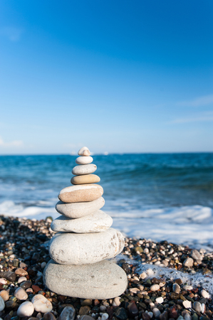 Balanced rocks in stack on Mediterranean pebble beach with splashing blue waves on background. Summertime outdoors vertical closeup image with copy space.