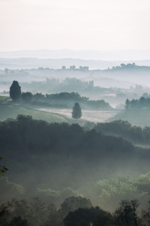 Impressive Tuscany foggy fields view at early morning. Colorful fall season at Italian countryside. Mountain background, Italy. Outdoors vertical image 版權商用圖片