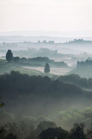 Indrukwekkende mistige velden in Toscane in de vroege ochtend. Kleurrijk herfstseizoen op het Italiaanse platteland. Bergachtergrond, Italië. Verticale afbeelding buitenshuis