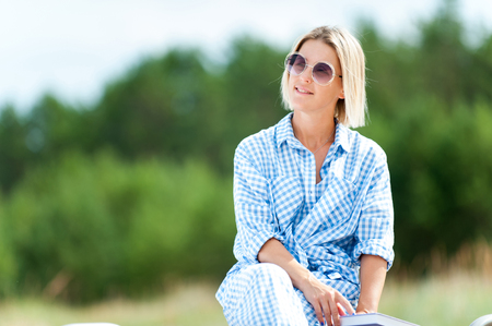 Pretty woman in sunglasses with book enjoying summer day. Outdoors summertime horizontal colored image