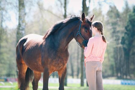 Giovane adolescente in piedi con il suo cavallo marrone preferito. Immagine di primavera orizzontale colorata all'aperto con filtro