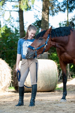 Young teenage girl enjoying of hugging her favorite chestnut horse with closed eyes. Colored outdoors vertical summertime image.