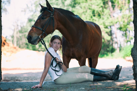Young teenage cheerful girl equestrian hugging her favorite chestnut horse. Vibrant multicolored summertime outdoors horizontal image with filter