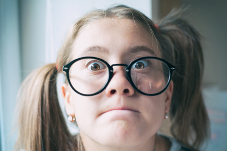 Portrait of glad funny surprised girl with ponytails in glasses. Indoors vibrant closeup horizontal image with filter.