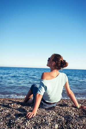 Young teenage fashionable girl resting sitting on Mediterranean Sea spectacular pebble coastline. Multicolored summertime outdoors vertical filtered image with blue sky background. View from backside. Stock Photo