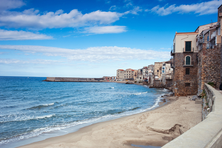 Cefalu, Sicily. Ligurian Tyrrenian Sea and sunny old town-medieval sicilian city. Province of Palermo, Italy. Summertime outdoors horizontal filtered image. Wide angle view with cloudy sky.