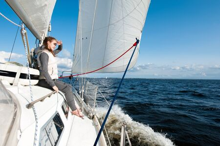Young lady looking forward having trip on sailing yacht at a speed swimming in wind through blue sea. Outdoors horizontal inspirational colored image. Vide angle view. Stok Fotoğraf - 129921235