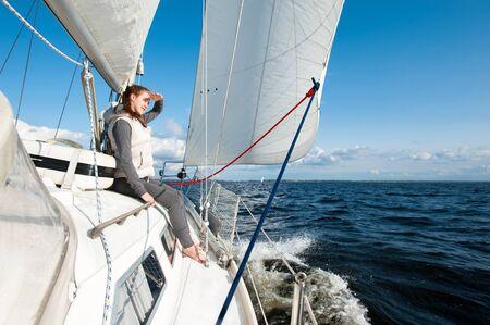 Junge Dame freut sich auf eine Fahrt auf einer Segelyacht mit einer Geschwindigkeit, die im Wind durch das blaue Meer schwimmt. Im Freien horizontales farbiges inspirierendes Bild. Blickwinkelansicht.