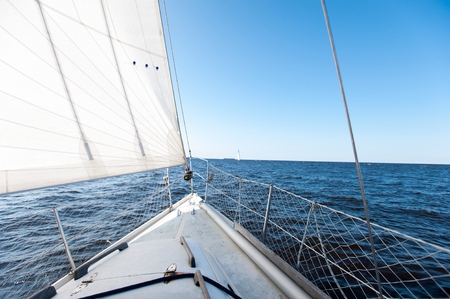 White sailing yacht at a speed swims to shore through blue sea. Outdoors horizontal inspirational colored image