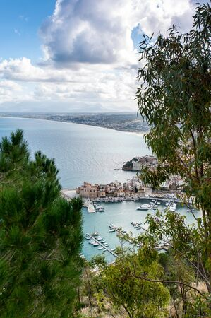 Castellammare del Golfo. Italy, Sicily. View from the mountain high above with pine tree. Calm blue sea, port, yachts and cloudy sky. Summertime outdoor vertical colored image. Banco de Imagens