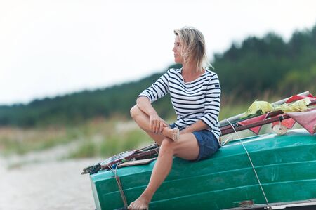 Attractive young woman sitting on wooden boat at windy seacoast and contemplating the sunset. Summertime outdoors horizontal colored inspirational image Reklamní fotografie