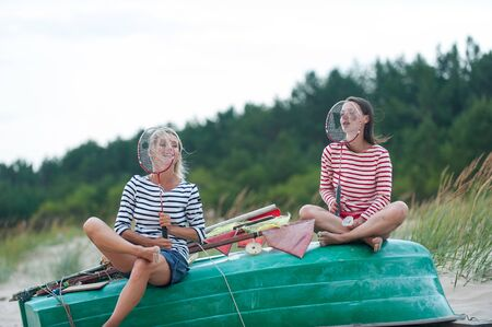 Two young women having fun sitting on wooden boat at summer windy seacoast. Friendssisters. Summertime outdoors inspirational horizontal image