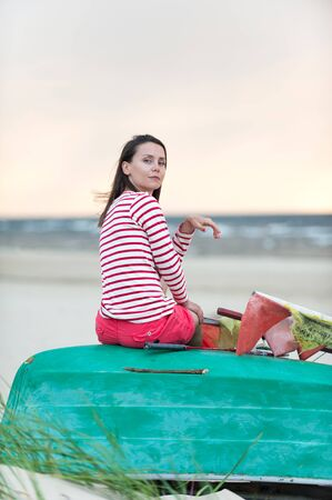 Attractive young woman sitting on beach at stormy waves. Summertime outdoors vertical colored inspirational image. View from backside Reklamní fotografie