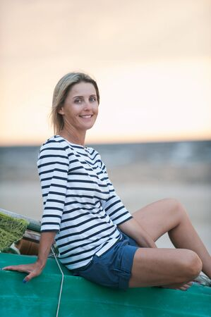 Attractive young woman sitting on beach at summer sunset sunlight. Outdoors vertical colored inspirational image. Reklamní fotografie