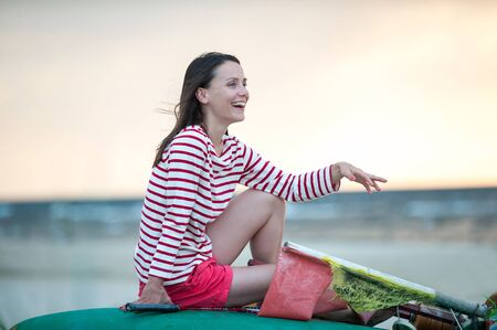 Attractive young woman sitting on beach at sunset sunlight. Summertime outdoors horizontal colored inspirational image. Reklamní fotografie