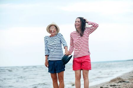Two young women have fun together on stormy seaside. Friendssisters. Summertime outdoors inspirational horizontal image. Spectacular cloudy sky background