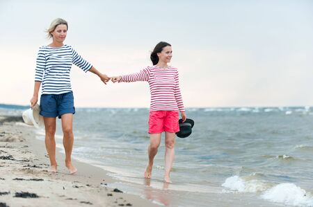 Two young women walking together holding hands on stormy seaside. Friendssisters. Summertime outdoors inspirational vertical image. Spectacular cloudy sky background Reklamní fotografie