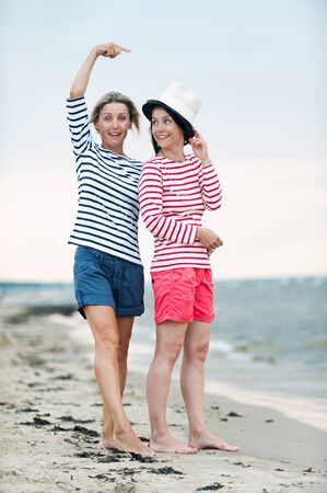 Two young women have fun together on stormy seaside. Friendssisters. Summertime outdoors inspirational vertical image. Spectacular cloudy sky background