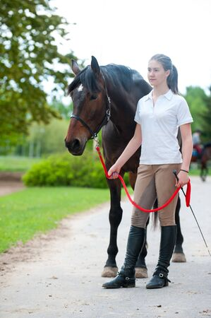Young teenage lady leads her favorite bay horse after training. Vibrant colored outdoors vertical summertime image.