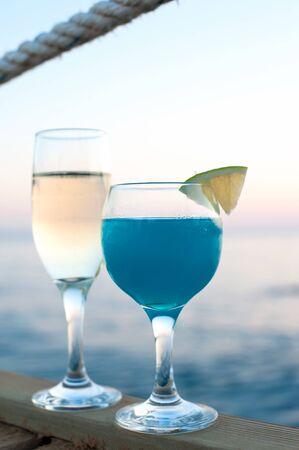 Twee glazen met witte wijn en verse blauwe cocktaildrank die zich op houten pijler bij zonsondergang bevinden. Levendige zomer buiten verticale afbeelding met blauwe oceaan achtergrond. Stockfoto