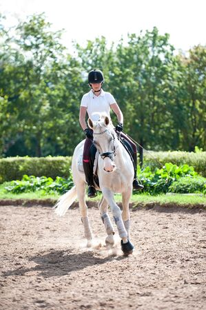 Young pretty teenage girl equestrian practicing horseback riding on manege. Outdoors summertime multicolored vertical image