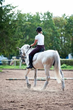 Young teenage girl equestrian practicing horseback riding on manege. Outdoors summertime multicolored vertical image. View from backside.