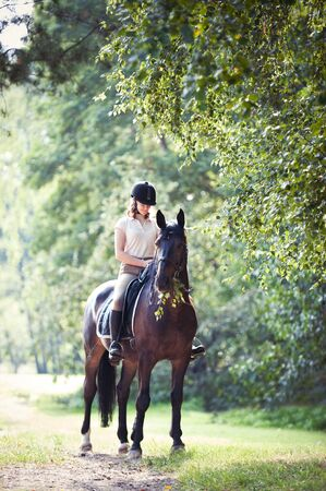 Young teenage girl equestrian riding horseback at spectacular early morning in rays of sunlight. Green trees frame. Multicolored vibrant outdoors vertical summertime image with vintage filter