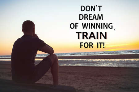 Don't dream of winning train for it. Sad lonely man sits and thinking on beach. Inspirational motivating quote. Multicolored outdoors horizontal image