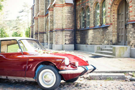 Part of old antique red retro car on ancient castle background. Side view. Colored outdoors horizontal image with filter.