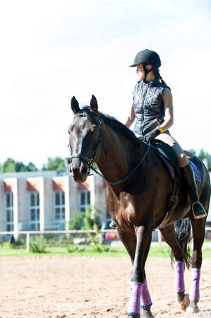 Teenage girl equestrian riding horseback at riding school place. Kleisti, latvia, Riga. Vibrant colored summertime outdoors vertical image.