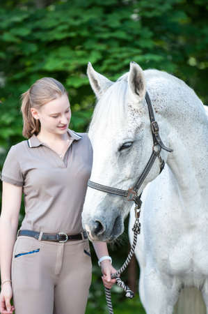 Pretty young teenage lady leads her favorite white horse in summer park. Vibrant colored outdoors vertical image. Foto de archivo