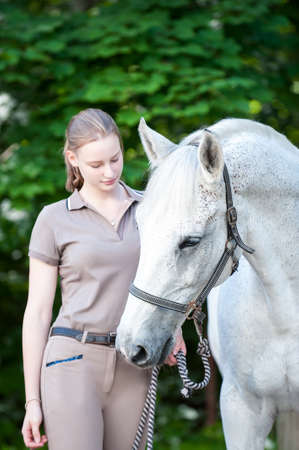 Pretty young teenage lady leads her favorite white horse in summer park. Vibrant colored outdoors vertical image.