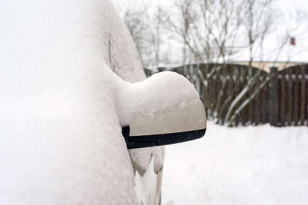 Car mirror covered of white snow. Outside. Outdoors horizontal winter-time image. Archivio Fotografico